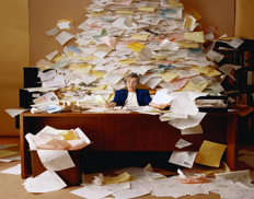 Woman buried in paper documents at her desk.